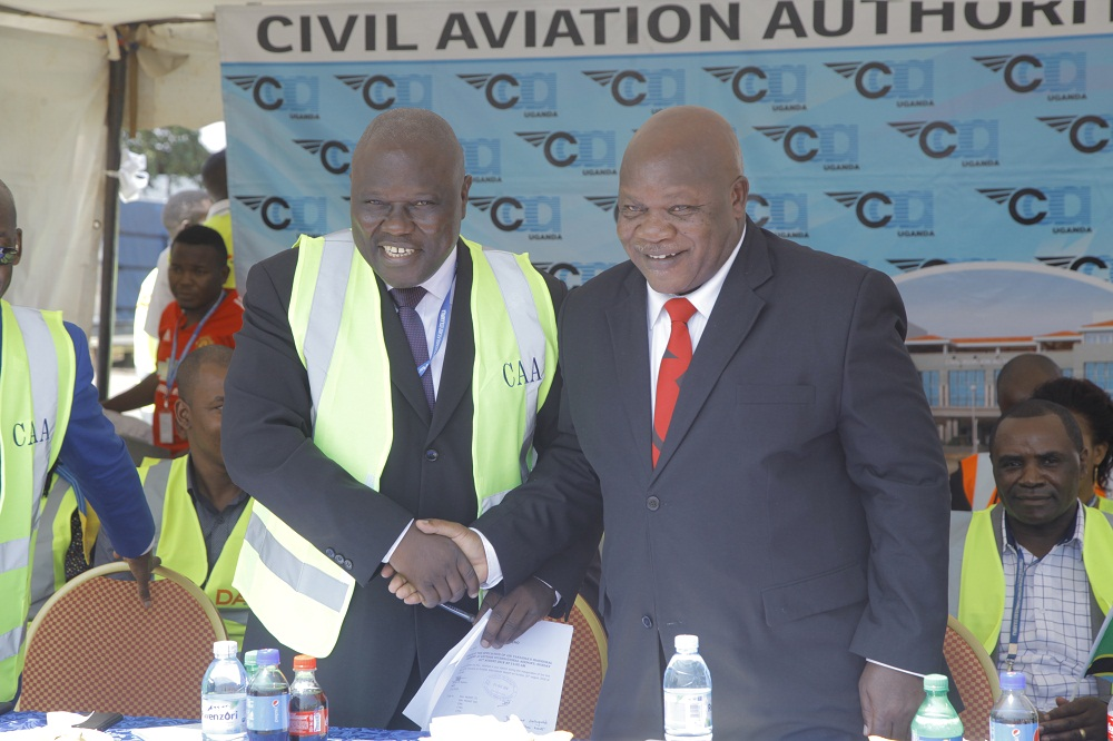 Aggrey Bagiire State Secretary for Work and Transport in Uganda (L) shakes hands with Hon. Kamwelwe Isack Aloyce Minister of Transport in Tanzania (R) during the launch of the first flight from Air Tanzania to Uganda on August 26, 2018 at Entebbe Airport. The 76-seater Q400 aircraft arrived at 13:01 and was received by stakeholders, officials from civil aviation authorities and Air Tanzania officials.