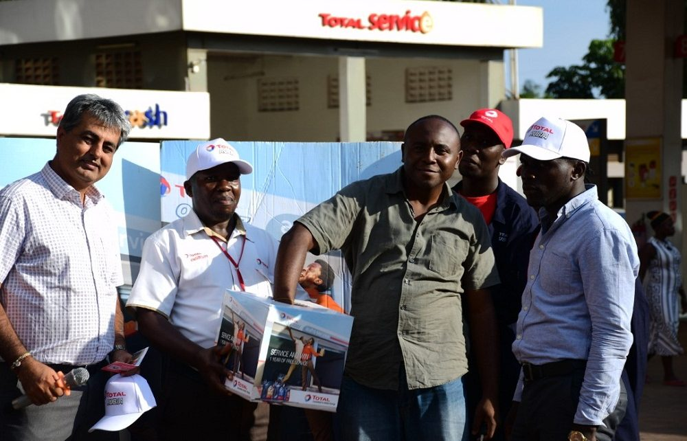 """Tushar Mashru (2nd L), Total Uganda dealer, Richard Jjuko, (C) Total Wampewo Station Manager, with a customer picking a raffle ticket during the Total Uganda """"Extra Mile"""" promotion on 2nd November 2018 at Total Wampeewo station. Lucky Winners of the draw will get free full-year car service."""