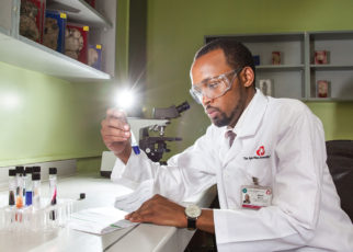 A laboratory technologist examines samples at the Aga Khan University Hospital Laboratory. In July 2003, the hospital became the first hospital in East Africa to be awarded the prestigious ISO 9001:2000 (now ISO 9001:2008) by the International Organization for Standardization,
