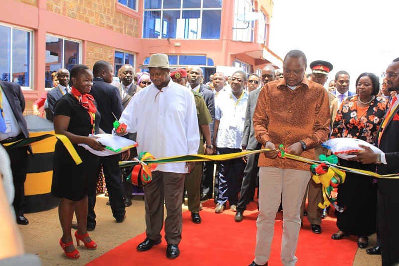 Uganda President Yoweri Museveni and his Kenya counterpart Uhuru Kenyatta cutting a ribbon in a recent function at the Busia border post as part of their mission to boost trade between the two countries at the one stop border post