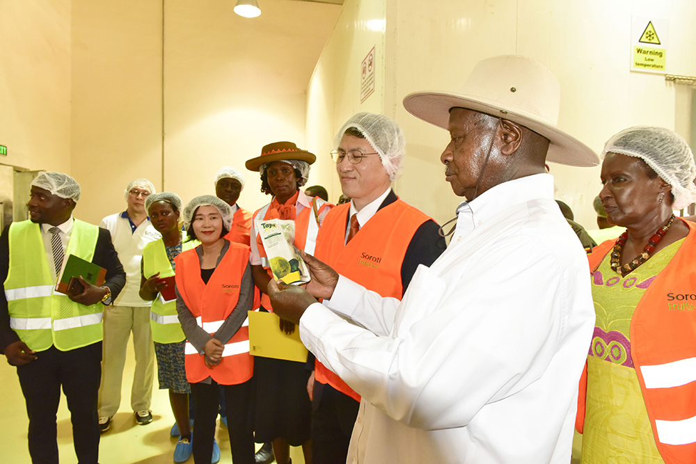 President Museveni accompanied by Trade and Industry Minister Amelia Kyambadde (R) looks at one of the processed and packaged products of Soroti Fruit Factory during the commissioning on Saturday April 13, 2019