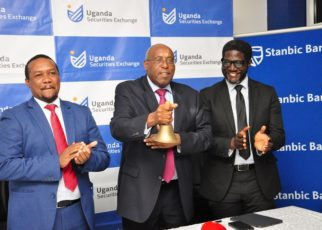 Mr Japheth Katto, the Chairman Stanbic Uganda Holdings Limited (centre) rings the bell as he officially re-opens trading on bourse under 'Stanbic Uganda Holdings Ltd'. Cheering on is Paul Bwiso CEO Uganda Securities Exchange and Sam Mwogeza the Stanbic Chief Finance Officer. Stanbic Bank Holdings Limited is now referred to as 'Stanbic Uganda Holdings Limited' with the banking business (Stanbic Bank Uganda Limited) now under the banking subsidiary.