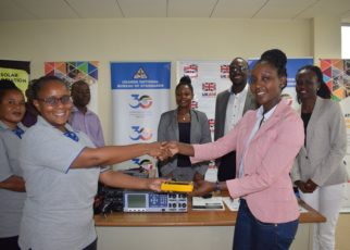 UNBS acting Executive Director Patricia Ejalu (Left) receiving the gadgets from DFID Programme Manager Lydia Nandawula during the event